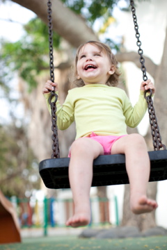 Little girl on a swing laughing
